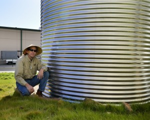 Horticulture manager, Randy Johnson, next to rainwater collection tank