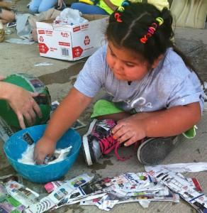 Little girl makes a papier-mâché ball for the chimpanzee enrichment.