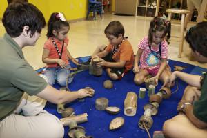 Preschool children build a wood and coconut mobile device for giraffe enrichment.