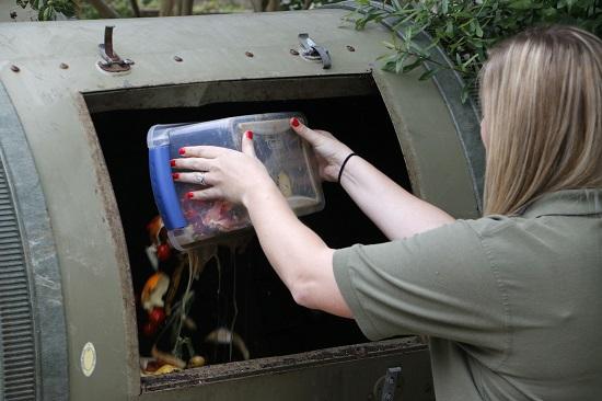 Youth Volunteer Coordinator Courtney Jonescu dumps some lunch scraps into a tumbling composting bin.