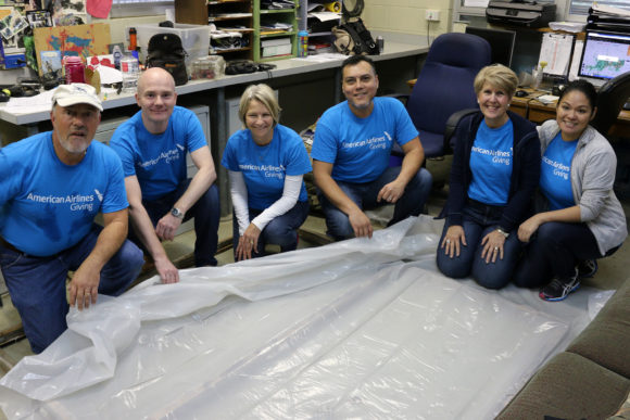Volunteers from American Airlines work on winter window coverings for our gorilla building.